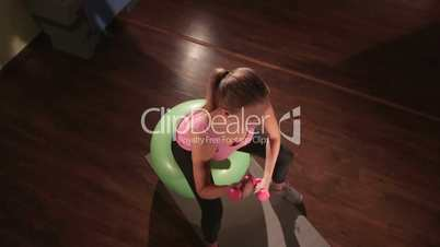 High-angle shot of fit woman exercising with light weight dumbbells in gym