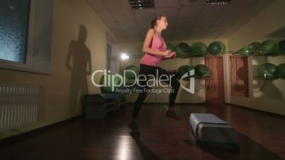 JIB CRANE: Fit young woman doing step aerobics exercise in fitness club