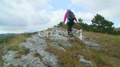 JIB CRANE: Woman day hiking in Crimean mountains walking along edge of cliff