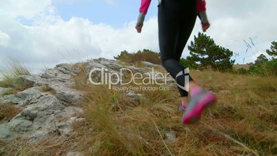 Woman hiker reached high point mountain plateau raising hands on edge of cliff