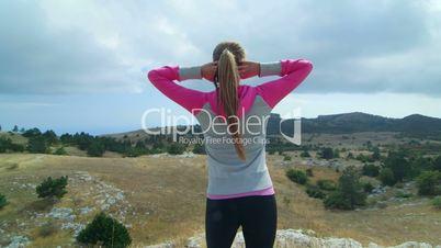 JIB CRANE: Fit young woman in sportswear on top of mountain plateau