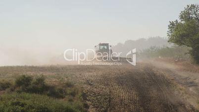 Farmer using modern farm tractor with disk harrows for harrowing field