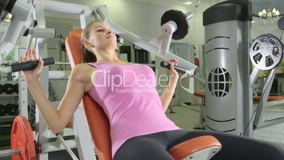woman lifting too much weight on chest press machine in health fitness club