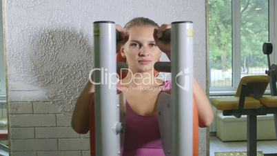 Woman training on weight exercise machine in fitness club looking at camera