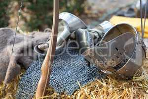 A silver metal helmet, gloves, mesh vest and bow lying in straw