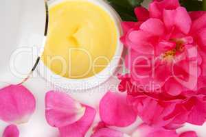 Open jar with the cosmetic cream and rose petals isolated on whi