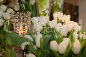 Crystal candle holder surrounded by white tulips