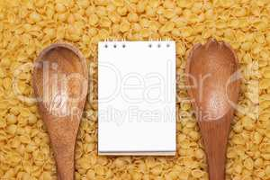 wooden spoons on dry uncooked macaroni background