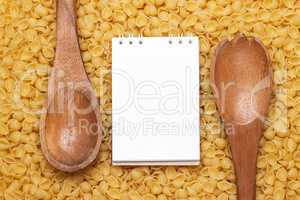 wooden spoons on uncooked macaroni background