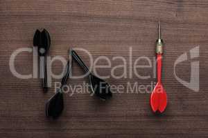 red dart uniqueness concept on wooden background