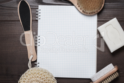 bath accessories and blank notepad over wooden background