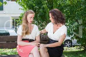 Zwei Frauen, in einem herzlichen Gespräch auf einer Bank