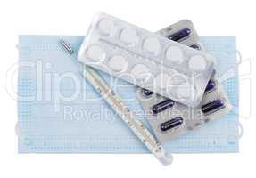 Tablets and capsules in blister packs with a thermometer lying on the face mask
