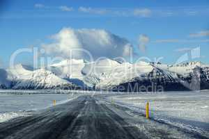 Snowy road with volcanic mountains in wintertime