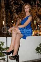 Junge Frau nachts im blauen Kleid draußen