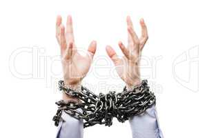 Businessman with metal chain tied hands raised for rescue help