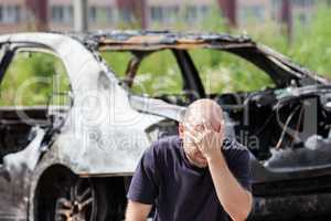 Crying upset man at arson fire burnt car vehicle junk