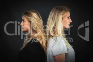 2 blonde Mädchen stehen Rücken an Rücken