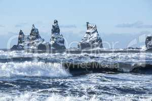 Three pinnacles of Vik with rough waves, South Iceland