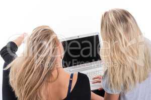 2 blonde Mädchen in Rückansicht vor dem Laptop