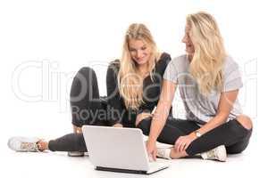 2 blonde Mädchen schauen gemeinsam in einen Laptop