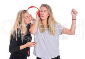 2 Freundinnnen teilen einen Kopfhörer und lauschen der Musik