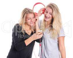 Zwei blonde Mädchen hören zusammen Musik über einen Kopfhörer