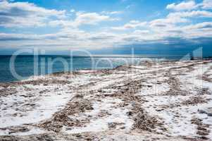Dirty ice field near water under partly cloudy blue sky