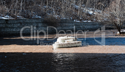 Chunk of ice illuminated in shallow river