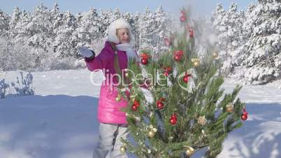 Child decorating Christmas tree in snow covered winter forest