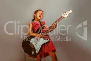Girl European appearance ten years playing guitar on a blue  bac