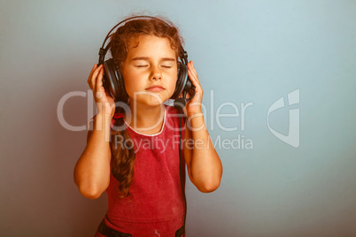 Teen girl child eyes closed listening to music with big headphon