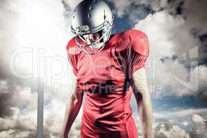 Composite image of american football player looking down while s