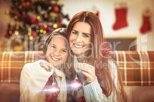 Festive mother and daughter holding baubles