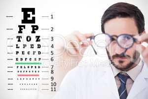Composite image of doctor wearing lab coat looking through eyegl