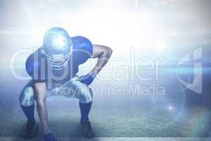 Composite image of american football player in uniform bending