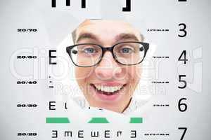 Composite image of geeky hipster smiling through hole