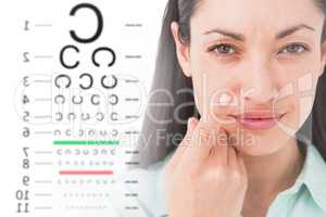 Composite image of brunette holding contact lens and smiling at