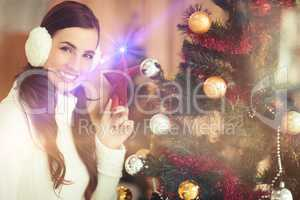 Smiling brunette holding star near a christmas tree