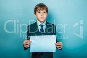 European appearance teenager boy in a business suit holding a wh