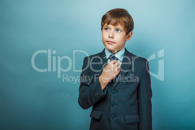 European appearance teenager boy in a business suit straightens