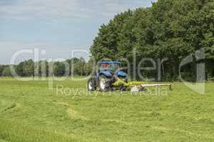 Agriculture, pasture mowing with blue tractor .