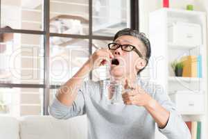 Mature 50s Asian man eating medicine