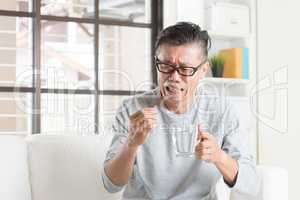 Mature Asian Chinese man eating medicine