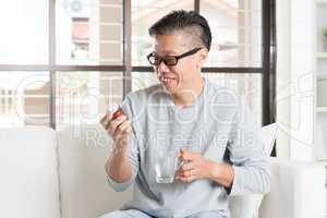 Asian man eating vitamins