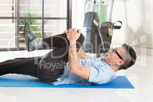 Mature Asian man exercise at gym