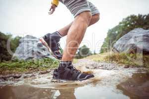 Man splashing in muddy puddles