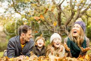 Smiling young family throwing leaves around