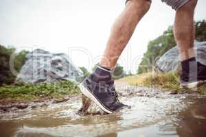 Man walking in muddy puddles
