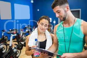 Trainer and athlete reading workout plan